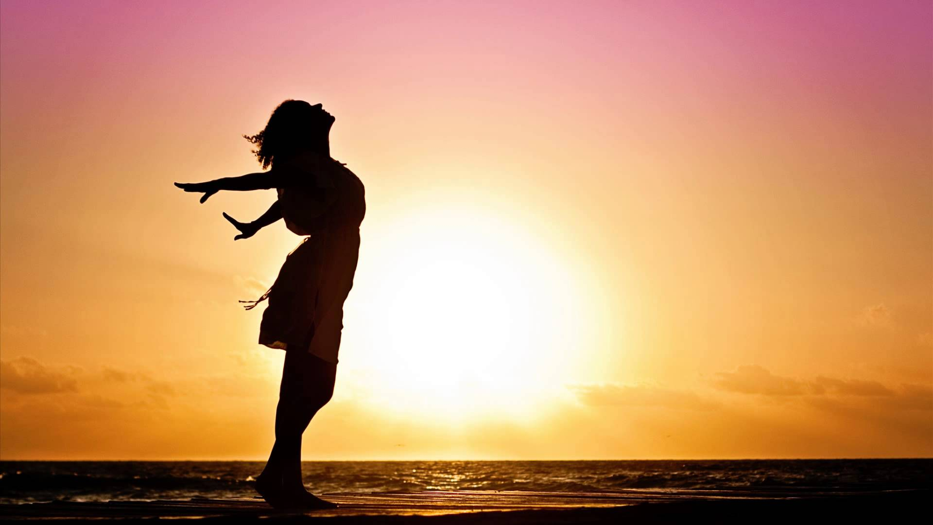 A young girl stand with the beautiful sun set