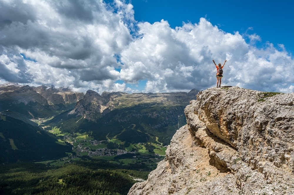 A girl stand on the highest rock and see the beautiful of the world